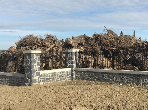 A pile of tree roots and pieces sits behind a prefab stone and metal fence.