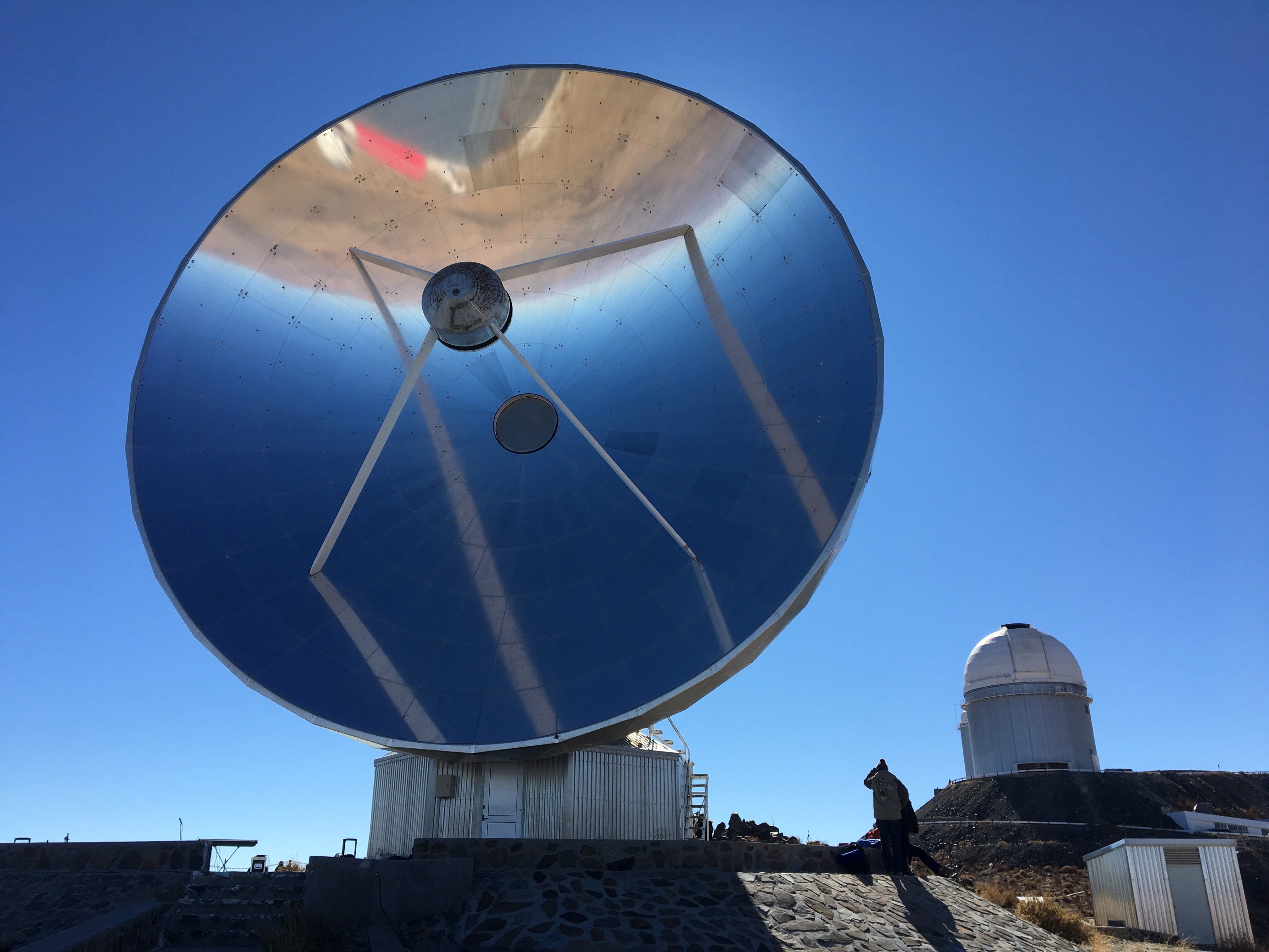 A mirrored dish and telescope dome at La Silla observatory, Chile.