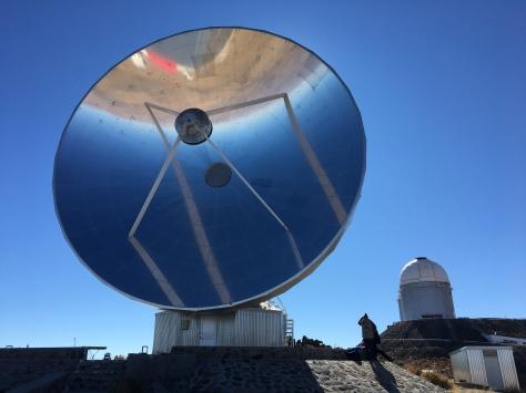A mirrored dish and telescope dome at La Silla observatory, Chile.