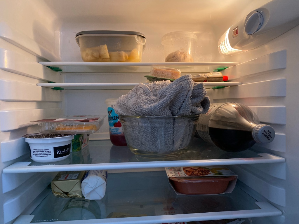 Inside a fridge, with sundry contents.